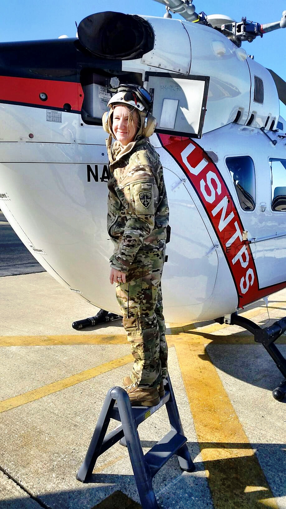 Here Sylvia Grandstaff, CW3 (USA), poses next to a USN Test Pilot School helicopter prior to a syllabus test flight.